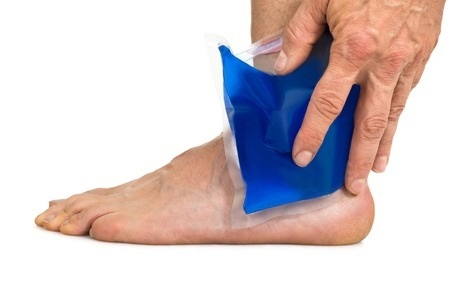 35462504 - close-up of hand holding cool gel pack on ankle over white background
